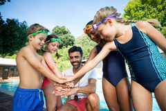 Instructor and children stacking hands at poolside. Male instructor and children stacking hands at poolside Stock Images