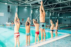 Instructor with children stands near water. In pool and preparing for diving. Trainer shows kids exercise, view from back. Modern sports center on background Royalty Free Stock Images