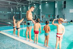 Instructor with children stands near water. In pool and preparing for diving. Trainer shows kids exercise, view from back. Modern sports center on background Stock Image