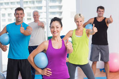 Instructor with class gesturing thumbs up at gym Stock Image
