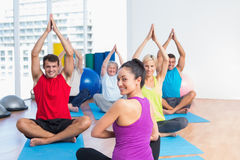 Instructor with class practicing yoga in fitness studio Royalty Free Stock Photos