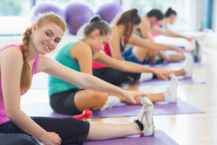 Instructor with class stretching legs in exercise room Royalty Free Stock Image