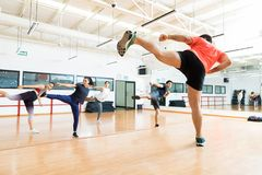 Instructor And Clients Kickboxing In Dance Class At Gym. Full length of male instructor and clients kickboxing in dance class at gym royalty free stock images