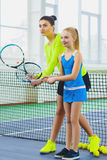 Instructor or coach teaching child how to play tennis on a court indoor Royalty Free Stock Images