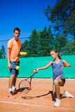 Instructor or coach teaching child how to play tennis on a court indoor.  Stock Photography