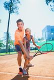 Instructor or coach teaching child how to play tennis on a court indoor Royalty Free Stock Image