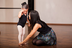 Instructor comforting a student. Female dance instructor trying to comfort one of her little students during a ballet class Stock Images