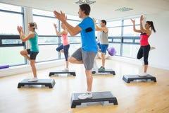Instructor con la clase de la aptitud que realiza ejercicio de los aeróbicos del paso Foto de archivo