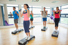 Instructor con la clase de la aptitud que realiza ejercicio de los aeróbicos del paso con pesas de gimnasia Foto de archivo