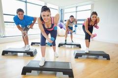 Instructor con la clase de la aptitud que realiza ejercicio de los aeróbicos del paso con pesas de gimnasia Foto de archivo libre de regalías