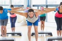 Instructor con la clase de la aptitud que realiza ejercicio de los aeróbicos del paso con pesas de gimnasia Imagen de archivo