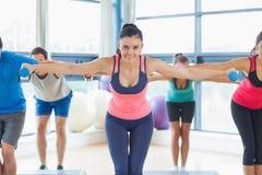 Instructor con la clase de la aptitud que realiza ejercicio de los aeróbicos del paso con pesas de gimnasia Fotos de archivo libres de regalías