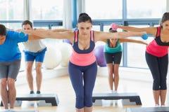 Instructor con la clase de la aptitud que realiza ejercicio de los aeróbicos del paso con pesas de gimnasia Imagen de archivo libre de regalías