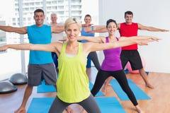 Instructor con la clase que ejercita en club de fitness Fotos de archivo