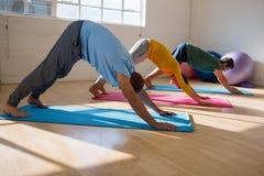 instructor con los estudiantes que practican actitud boca abajo del perro en estudio de la yoga Fotografía de archivo