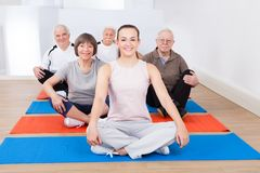 Instructor confiado con los clientes mayores en el gimnasio Imágenes de archivo libres de regalías