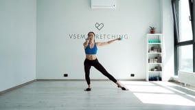 Instructor de la aptitud que hace posiciones en cuclillas con pesas de gimnasia y que desliza discos en la cámara lenta almacen de metraje de vídeo