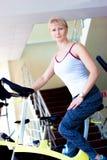 Instructor de la bici de la mujer de la aptitud en el gimnasio Imágenes de archivo libres de regalías