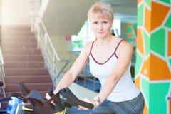 Instructor de la bici de la mujer de la aptitud en el gimnasio Imagenes de archivo