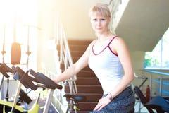 Instructor de la bici de la mujer de la aptitud en el gimnasio Imagen de archivo