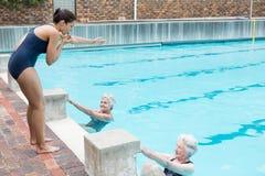 Instructor de la natación que ayuda a mujeres mayores Fotos de archivo