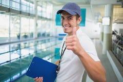Instructor de la natación que sonríe en la cámara por la piscina fotos de archivo