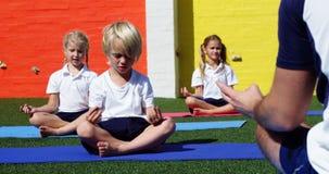 Instructor de la yoga que da instrucciones a niños en la ejecución de yoga almacen de metraje de vídeo