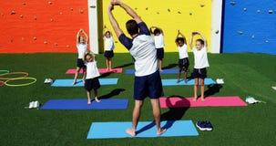 Instructor de la yoga que da instrucciones a niños en la ejecución de ejercicio metrajes