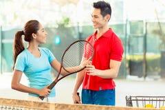 Instructor del tenis que enseña un jugador del principiante al apretón correcto imagen de archivo libre de regalías
