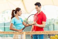 Instructor del tenis que enseña un jugador del principiante al apretón correcto foto de archivo