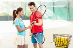 Instructor del tenis que enseña un jugador del principiante al apretón correcto fotos de archivo