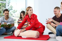 Instructor demonstrating CPR on mannequin at first aid class stock photo