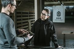 Instructor describing gun to female client. In shooting range stock photography