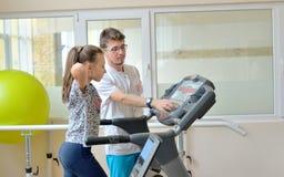 Instructor en gimnasio con la niña imagenes de archivo