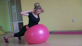Instructor en la ropa de deportes que hace ejercicios traseros de la desviación con el fitball 4k almacen de video