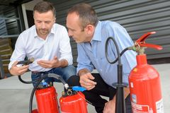 Instructor explaining how to use fire extinguisher. Fire stock photos