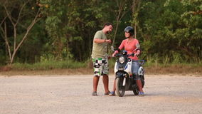 Instructor explains right way of driving scooter to girl stock footage