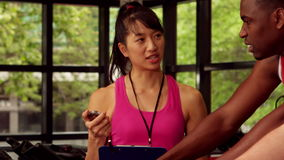 Instructor femenino feliz que ayuda a hombres mientras que biking metrajes