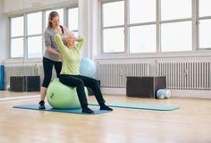 Instructor femenino que ayuda a la mujer mayor que ejercita en gimnasio Fotografía de archivo libre de regalías