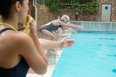 Instructor femenino que silba mientras que mujeres mayores que se zambullen en piscina Imagenes de archivo