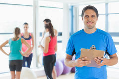 Instructor with fitness class in background in fitness studio Stock Image