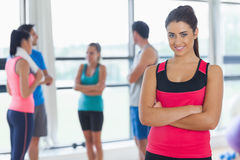 Instructor with fitness class in background in fitness studio Stock Photos