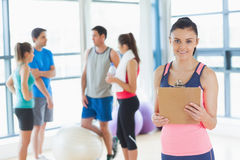 Instructor with fitness class in background in fitness studio Royalty Free Stock Images