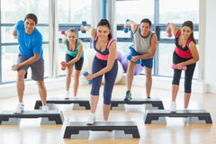 Instructor with fitness class performing step aerobics exercise with dumbbells Royalty Free Stock Images