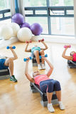 Instructor with fitness class performing step aerobics exercise with dumbbells Stock Image