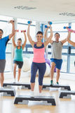 Instructor with fitness class performing step aerobics exercise with dumbbells Stock Photos