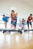 Instructor with fitness class performing step aerobics exercise with dumbbells Royalty Free Stock Photos