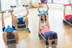 Instructor with fitness class performing step aerobics exercise with dumbbells Royalty Free Stock Photography