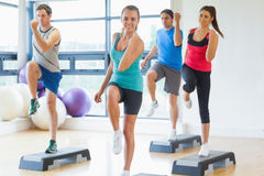 Instructor with fitness class performing step aerobics exercise Stock Photography