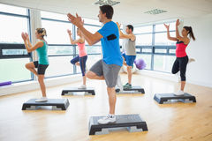 Instructor with fitness class performing step aerobics exercise Stock Photo